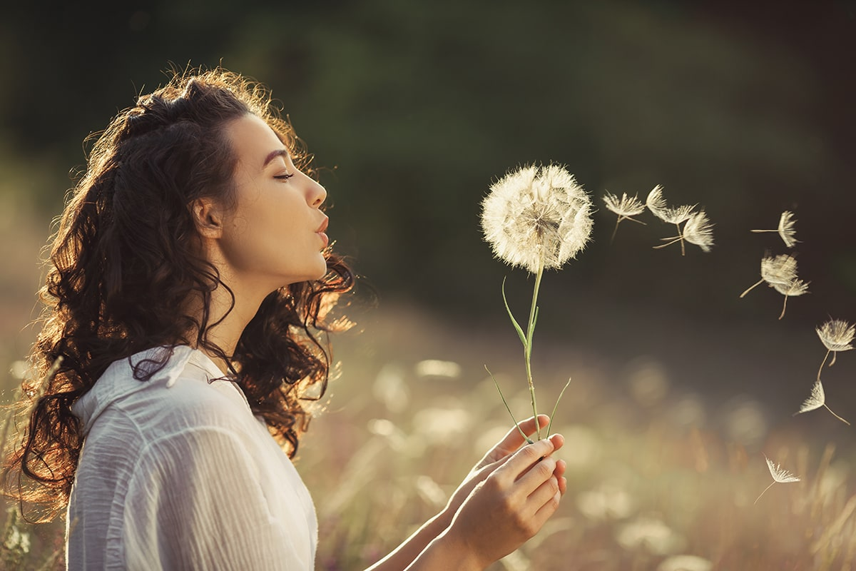 Woman with no allergies blowing dandelion seeds