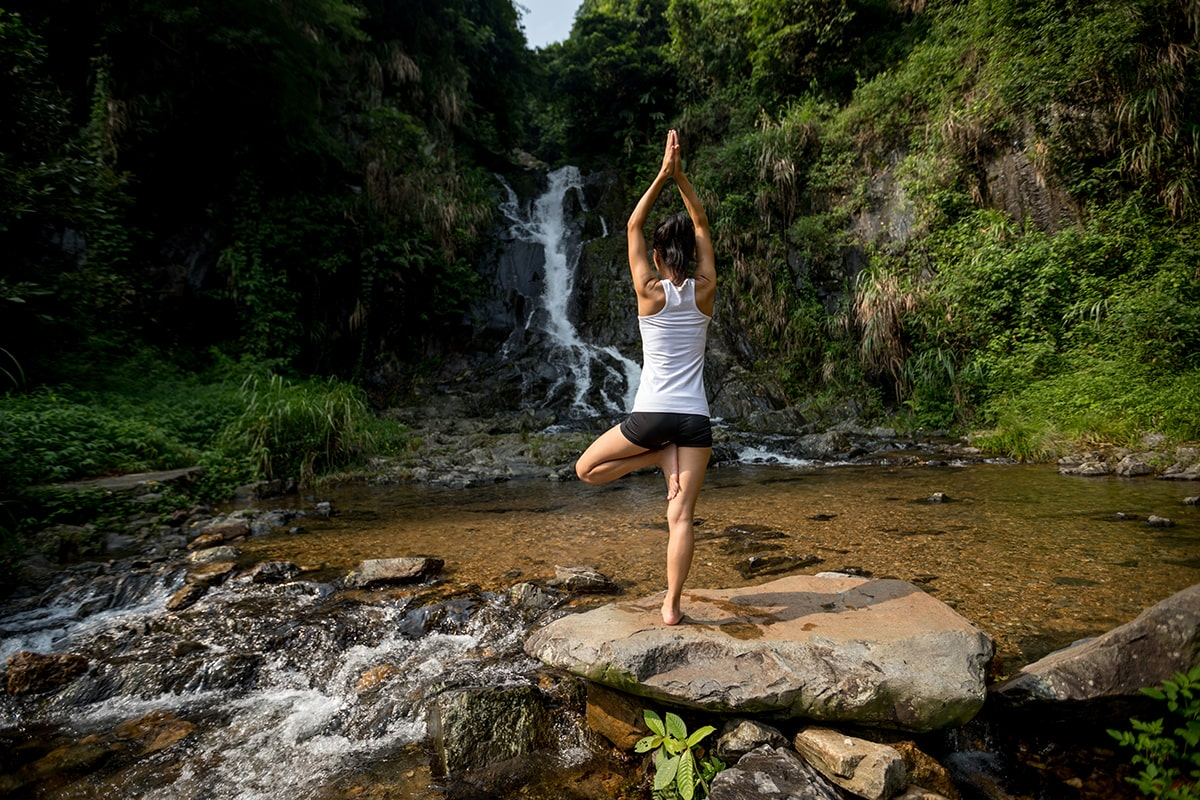 Woman doing yoga near a waterfall