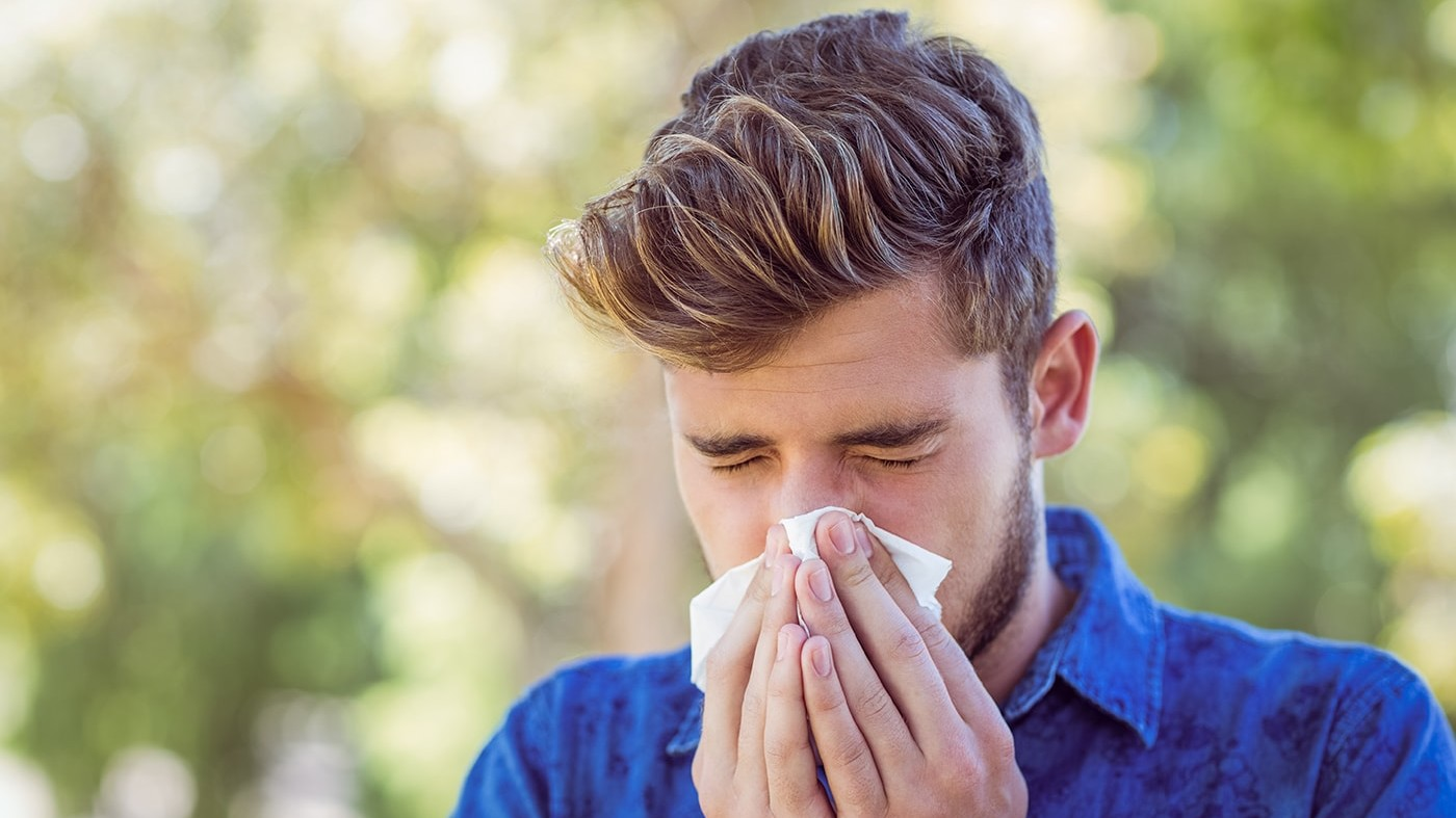 Man with allergies blowing his nose